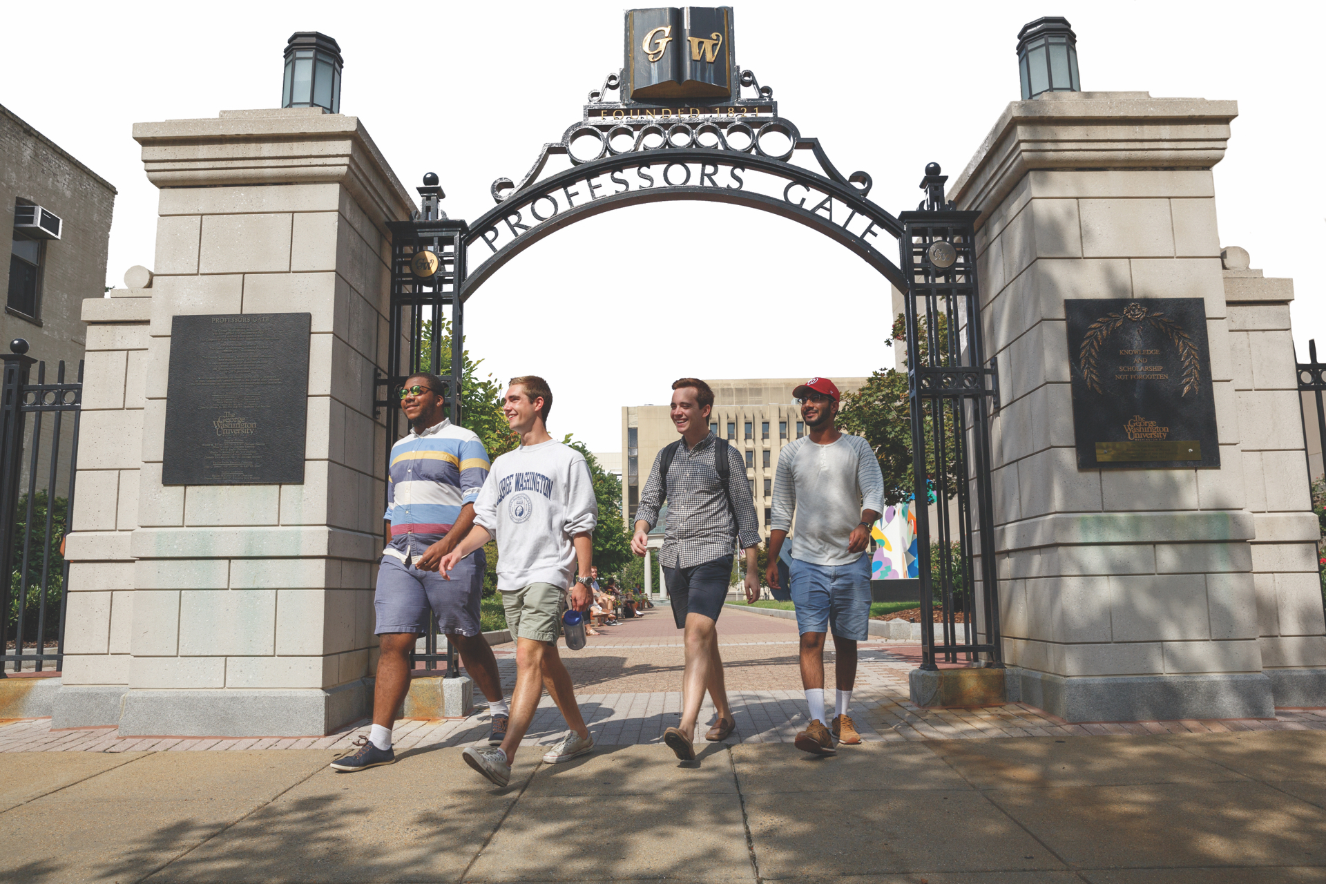 Four GW students walking under a GW gate