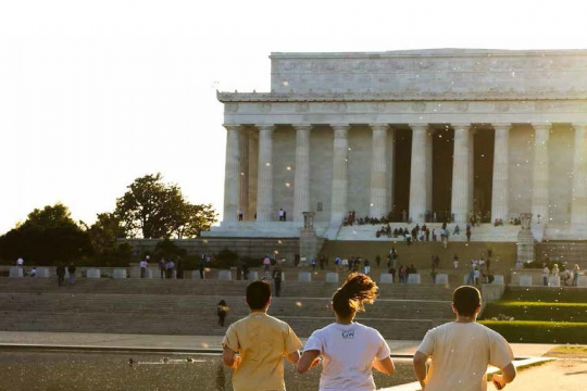 Three students running by reflecting pool towards Lincoln Memorial on the National Mall