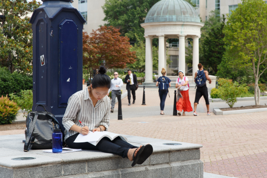 Student studying on campus in Kogan Plaza